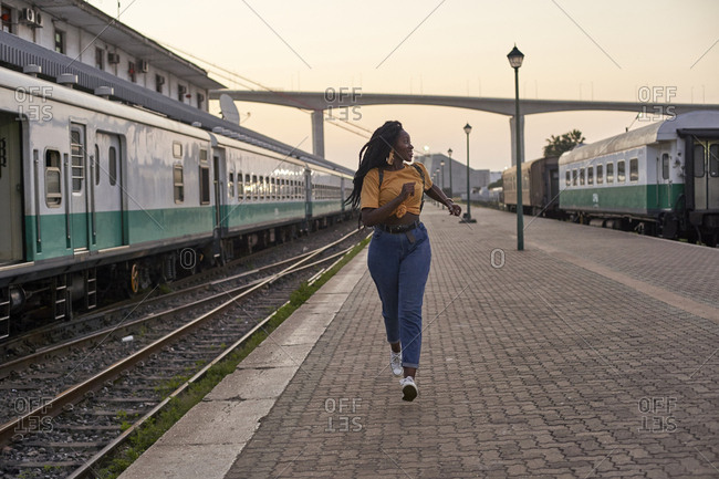 Young woman running on platform at the train station