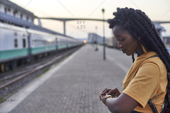 Young woman on platform at the train station checking her watch