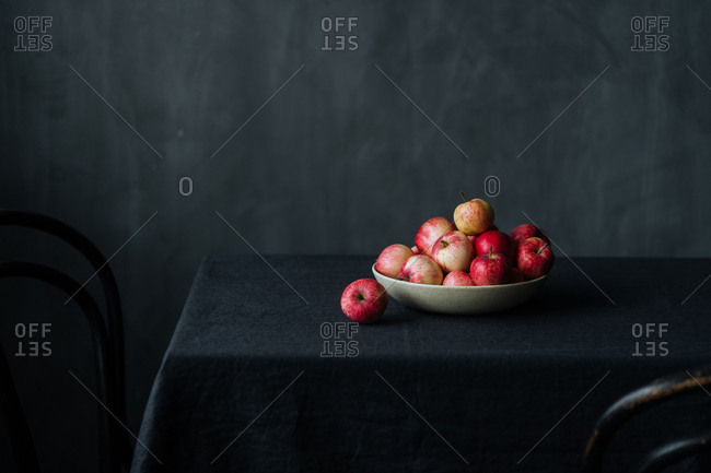 Bowl full of red apples on table with dark background