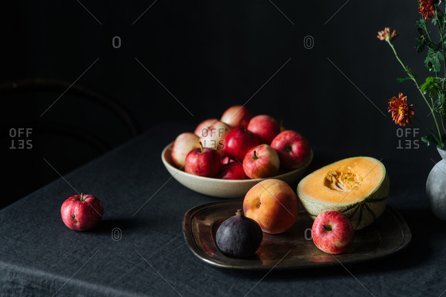 Fruit on tray and apples in a bowl on dark table