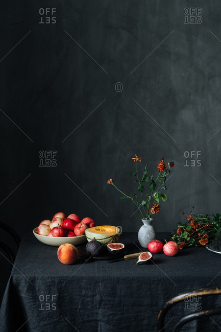 Fruit and flowers on table in front of dark background