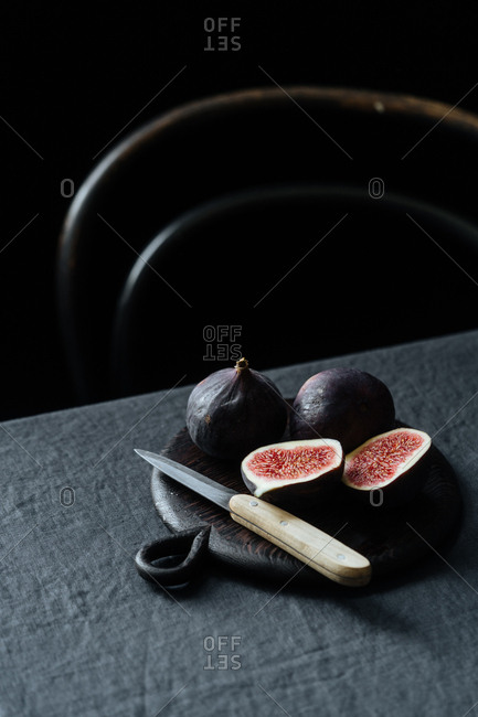 Sliced figs with knife on dark tablecloth