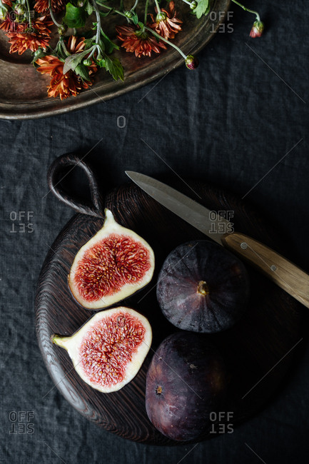 Overhead view of sliced figs on table with flowers