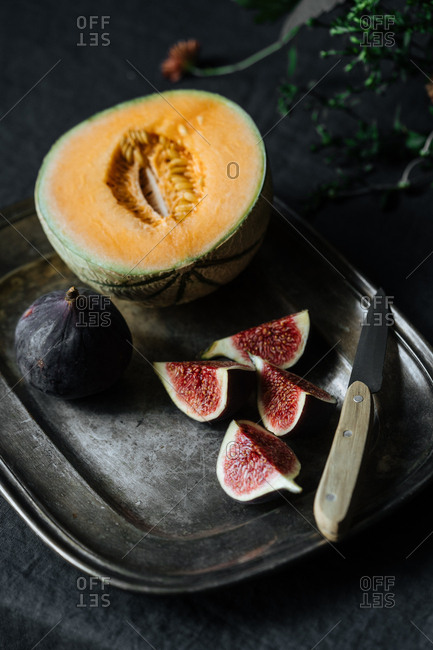 Overhead view of melon and figs on tray with knife