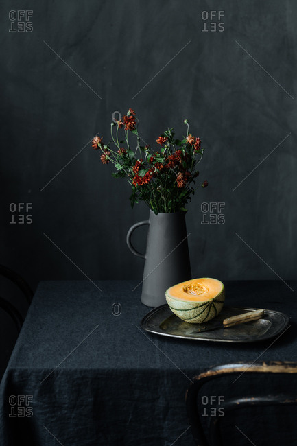 Melon on tray on table with flowers