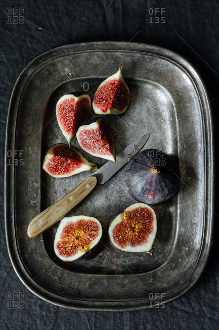 Overhead view of sliced figs on metal serving platter