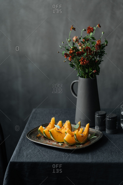 Plate with spiced melon on table by vase with flowers