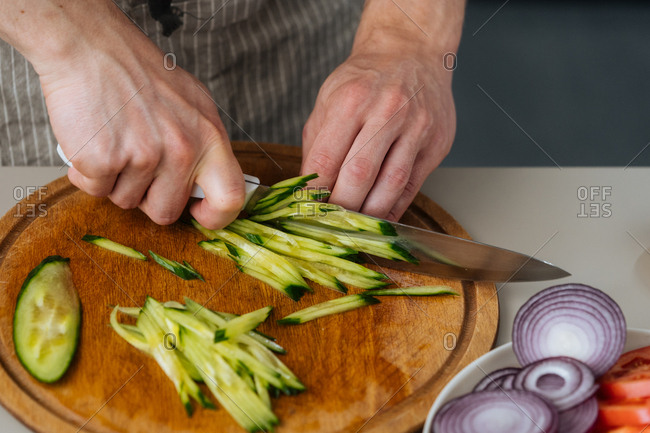 Cook chopping cucumber in sticks on wooden board with knife
