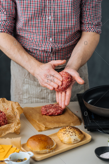 Chef in apron with stove and ingredients making burgers