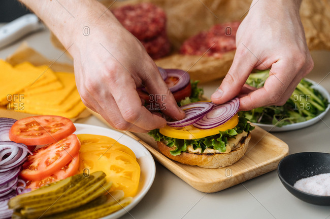 Hands of cook putting onion on grilled burger bun with sauce and vegetables