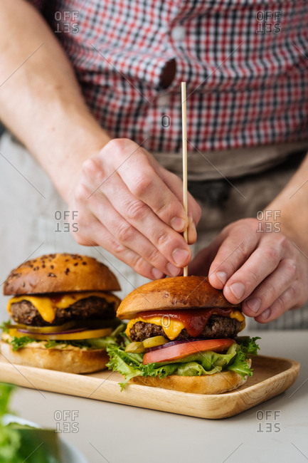 Cook standing at table making cheeseburger with stick in it
