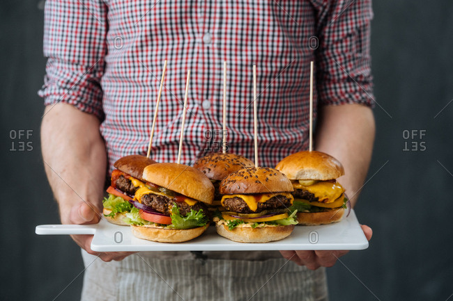 Cook holding board with appetizing cheeseburgers on sticks