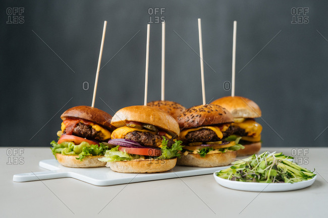Appetizing with sticks on a board on light table with grey background