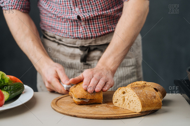 Cook in apron cutting bread with knife on wooden board