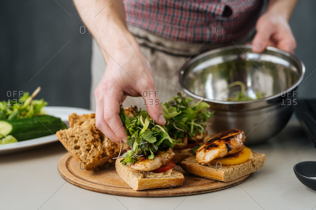 Cook putting green vegetables on bread pieces with chicken meat on wooden board