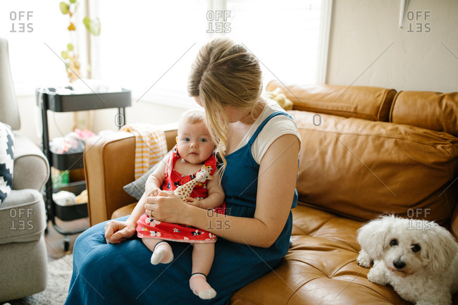 Mother holding her baby daughter on a sofa next to a dog