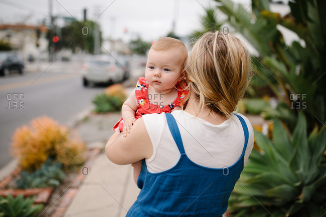 Mother walking down the sidewalk in the city with her baby girl