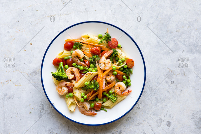 Pasta penne primavera vegetables with shrimp on a plate