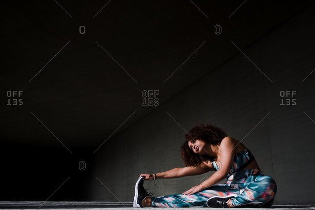 Curvy African American Woman Stretching After Working Out In Urban Area