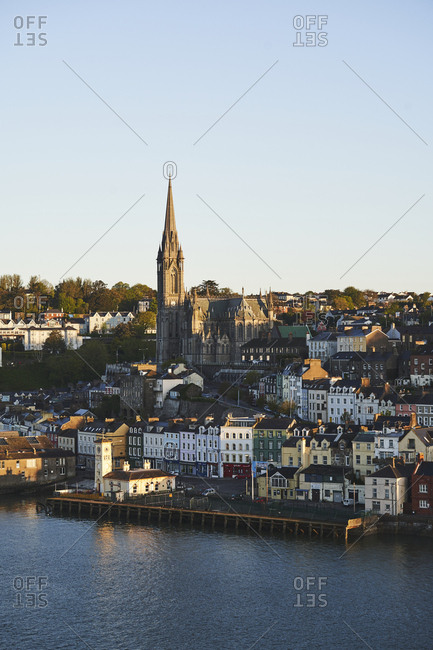 St. Coleman's Church or Cobh Cathedral in the morning light with the town of Cobh surrounding it as seen from the harbour front.