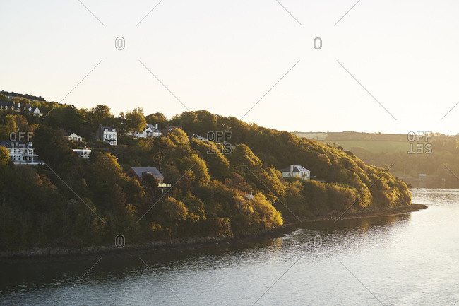 A few houses on the outskirts of Cobh, Ireland, with hills in the background in the early morning light.