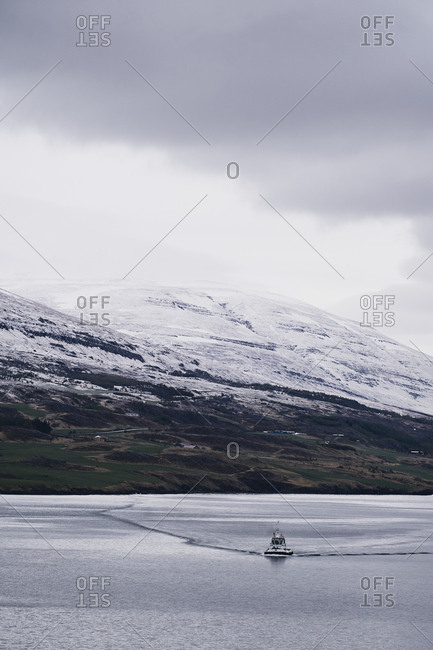 Eyjafjörður, Iceland - May 13, 2019: A view of a cross section of the Eyjafjörður in north Iceland with snow on the mountain tops blending into a cloudy white sky and a small boat on the calm water.
