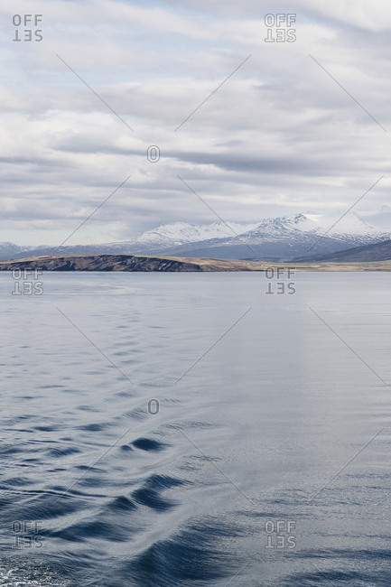 Eyjafjörður, Iceland - May 13, 2019: A view of the Eyjafjörður in north Iceland as seen from a cruise ship, with the wake of the ship rippling out into the distance and clouds in the snow capped mountain tops.