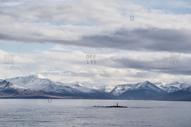 Eyjafjörður, Iceland - May 13, 2019: A view of the mountain sides of the Eyjafjörður in north Iceland with snow caps. The Hrólfssker lighthouse in the distance between the mountains.