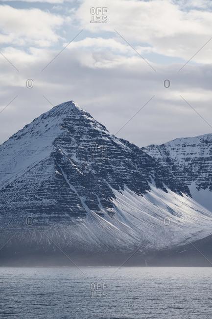 Eyjafjörður, Iceland - May 13, 2019: A view of the mountain sides of the Eyjafjörður in north Iceland with snow caps and sea mist.