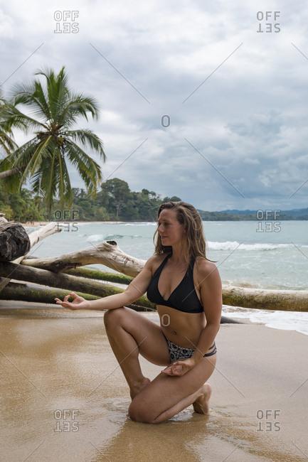 Woman doing yoga on a beach in Costa Rica