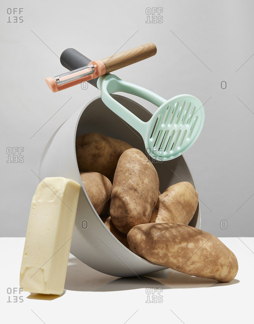 Butter, masher, and peeler piled on top of a tipped over bowl of potatoes
