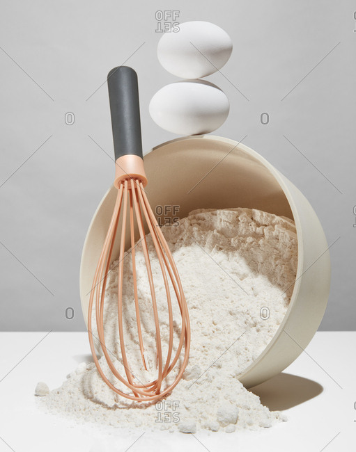 Two eggs and a whisk against a tipped over bowl of flour