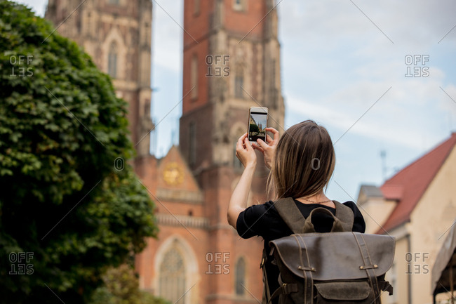 young girl with a smartphone on the background of the old church in Europe