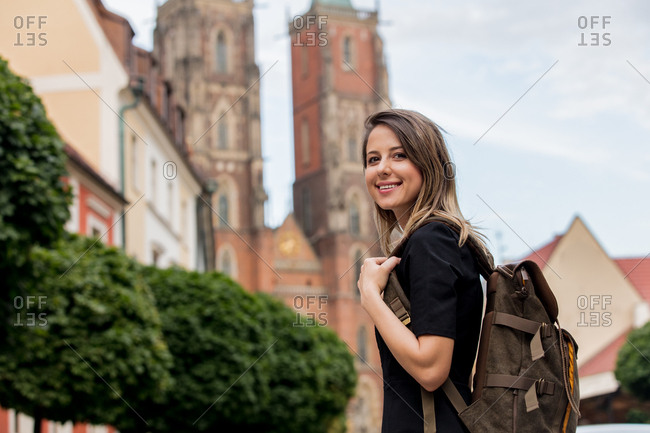 young girl with a backpack on the background of the old church in Europe