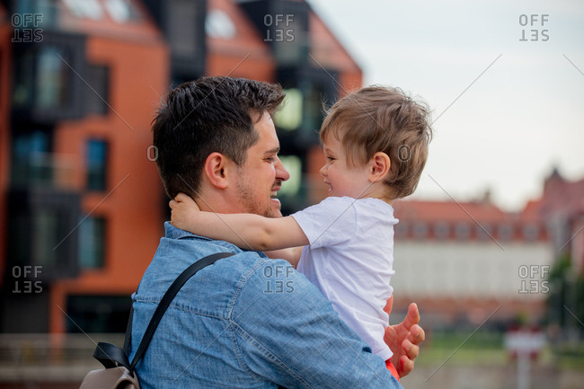 young dad holding his son in his arms is in the city