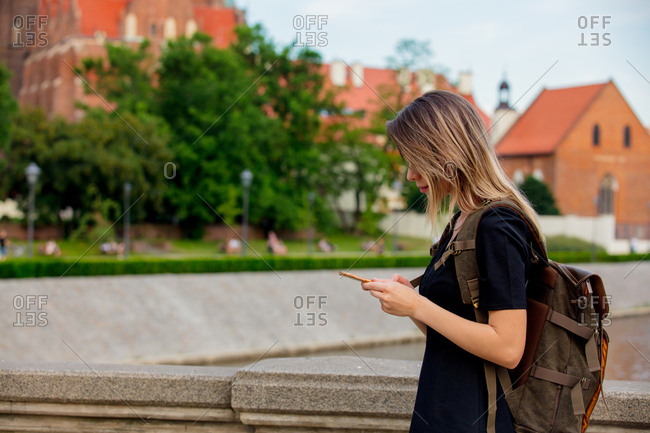 young girl with smartphone and backpack on the city street