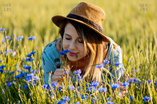 a young girl smelling flowers in the meadow