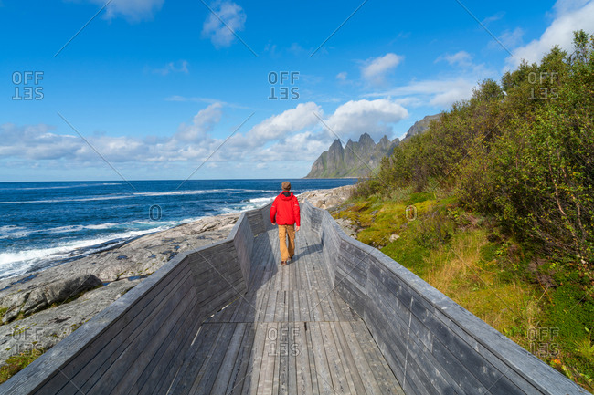 Man on walkway admiring The Devils Teeth, Okshornan Range, Tungeneset coastline, Senja Island, Troms, Norway