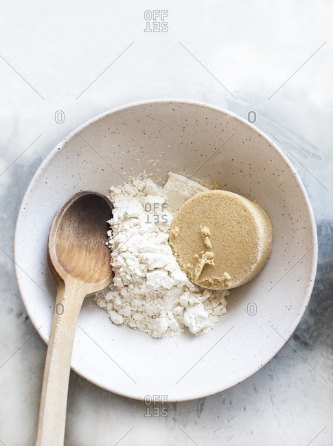 Ceramic bowl with flour, brown sugar and old wood spoon