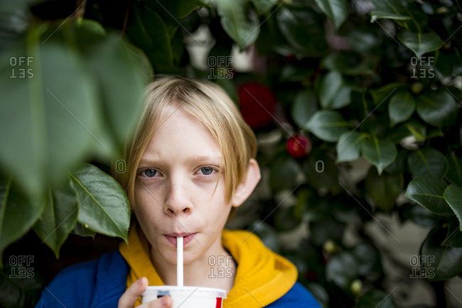 Teenage boy drinking from straw surrounded by green foliage