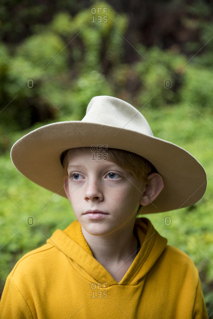 Young boy wearing large old hat