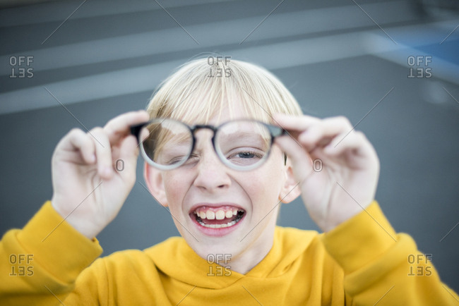 Young teenage boy playing with eyeglasses in front of his face