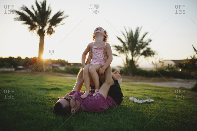 Father laying on grass holding his laughing daughter up on his legs