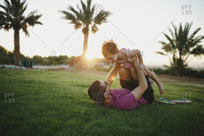 Father laying on grass holding his laughing daughter up in the air