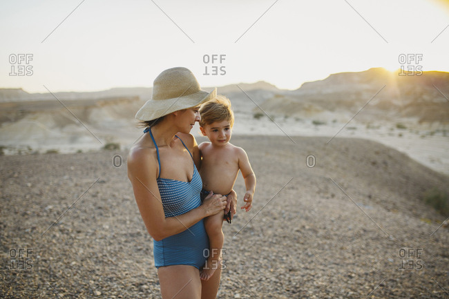 A mother wearing a hat holding her son in the desert during sunset