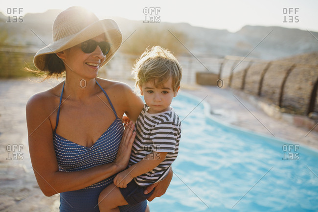 A mother wearing a hat holding her son in the pool during sunset