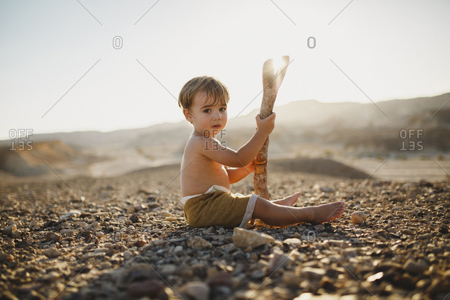 Toddler boy sitting on the desert's ground holding a branch