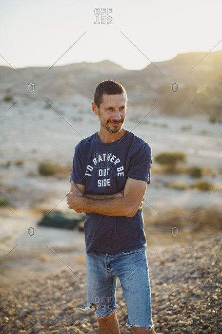 A young man standing in the desert looking forward in sunset