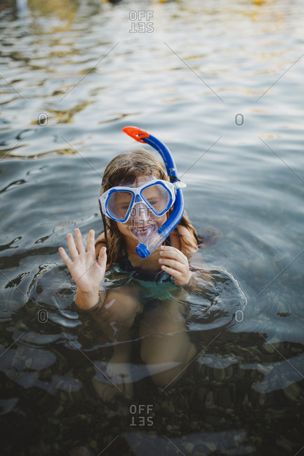 A girl wearing snorkel waving goodbye before  diving into the red sea