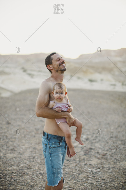 A father laughing while holding his baby girl in the desert